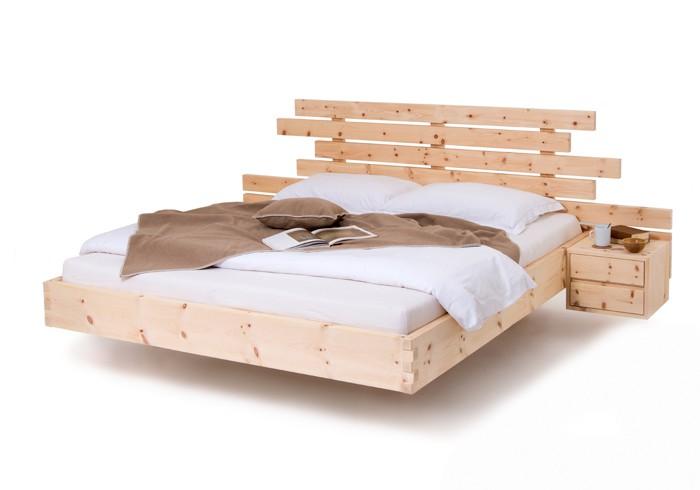 Am Foto zusehen das Zirbenbett Exklusive 100 von Schröcker Tischlerei GmbH gefertigt aus rein luftgetrockneten Zirbenholz aus den Nockbergen. Am Bild hat das Arvenbett auch seitlich zwei Stück Nachtkästchen Angebaut mit jeweils zwei Laden. Das Zirbenholzbett ist schwebend Ausgeführt beim Fußteil mit einer gezinkten Holzverbindung.