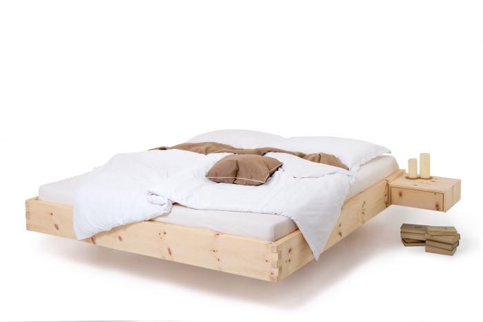 Am Bild das Zirbenholzbett Natur M9 aus rein luftgetrockneten Zirbenholz aus den Nockbergen. An das Arvenbett sind links und rechts Zirbenholznachtkästchen angebaut. Die Ausführung dieses Zirbenbett ist schebend.